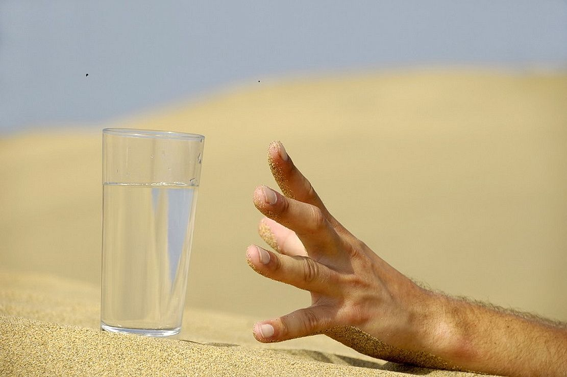 hand-reaching-for-a-glass-of-water-in-the-desert.jpg