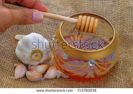 stock-photo-close-up-of-garlic-and-jar-with-honey-and-dipper-on-jute-healthy-eating-713780938.jpg